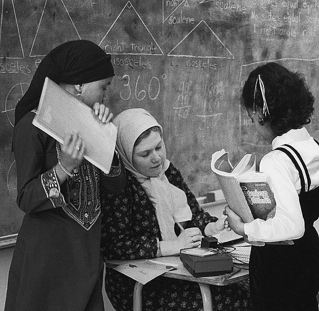 Caption: Sister Mary Abdi talking over homework assignments with Rohymah Toulas and Lanya Abdul-jabbar at the Islamic School in Seattle, Washington., Credit: Library of Congress.