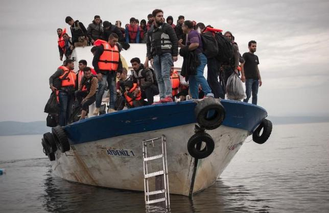 Caption: Migrants and refugees aboard a Turkish fishing vessel as they arrive on the Greek island of Lesbos after crossing part of the Aegean Sea. October 2015., Credit: Reuters | Fotis Plegas G