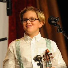 Caption: 9 year old Fiddlin' John Maupin electrifies the WoodSongs Stage.
