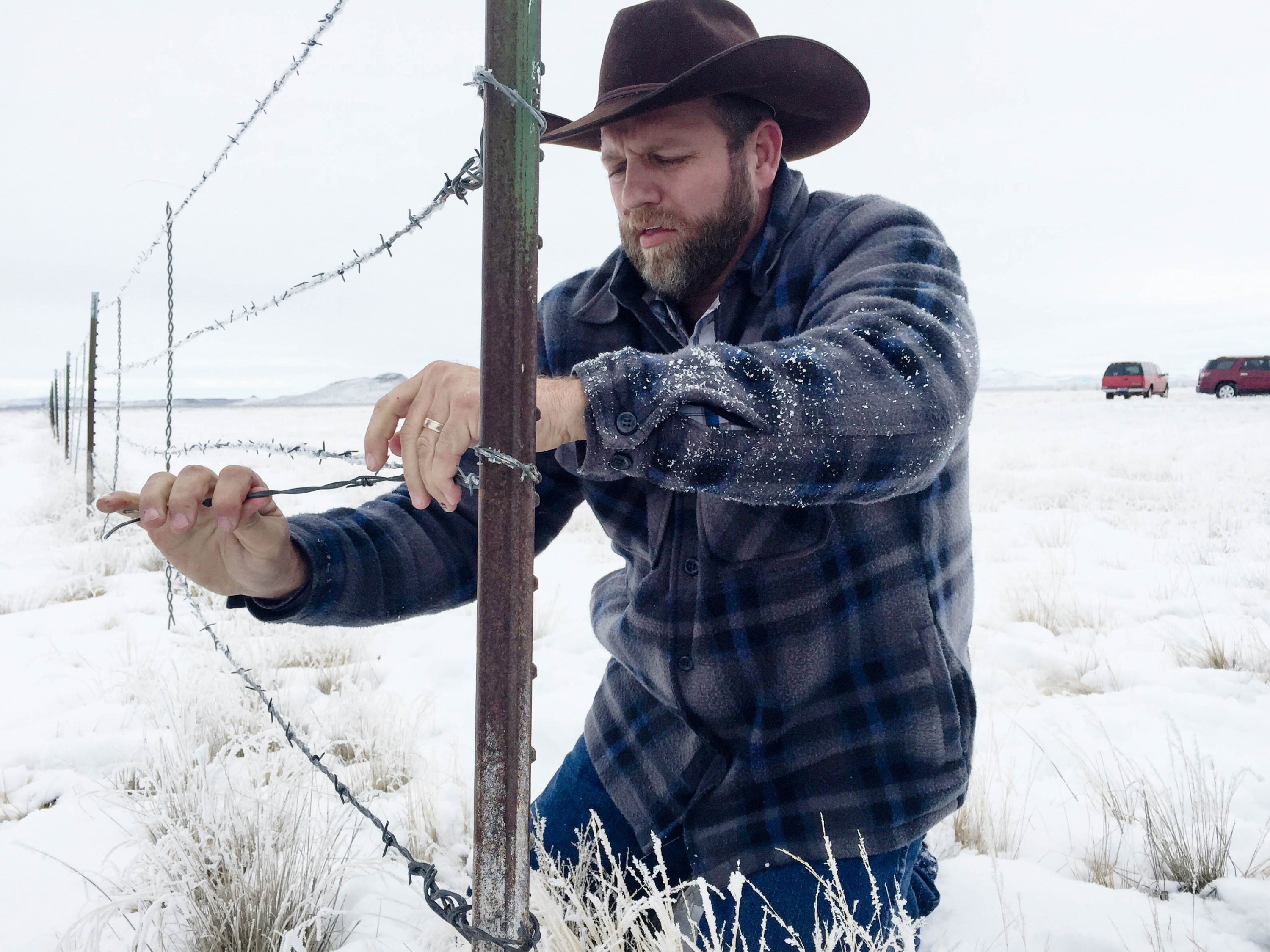 Caption: Ammon Bundy removes a fence from the Malheur National Wildlife Refuge in January., Credit: Jess Burns/OPB