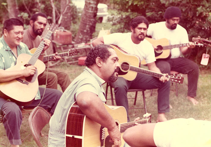 "Caption: Gabby Pahinui (center), playing music in his backyard with Leland ""Atta"" Isaacs (left), and his sons – Phillip, Cyril and Martin Pahinui (from left to right).  , Credit: Photo courtesy of the Pahinui Ohana."