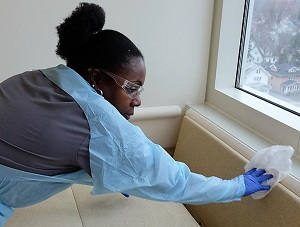 Caption: Environmental services worker Jeanna Hibbert scrubs the hospital room to get rid of C-diff bacteria., Credit: Michelle Faust/ Side Effects