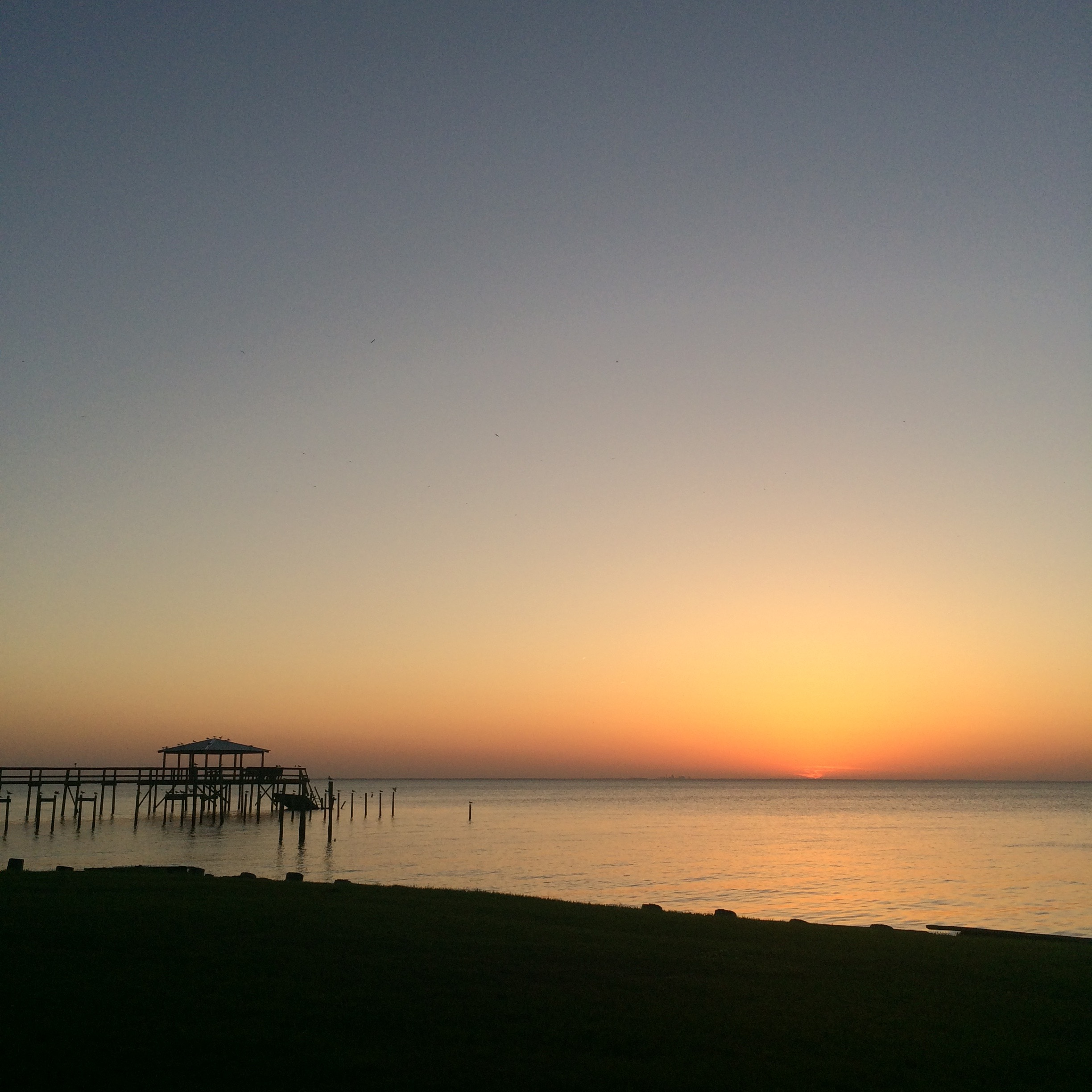 Caption: Sunset overlooking Mobile Bay in Fairhope, Alabama. , Credit: Photo by Tina Antolini.