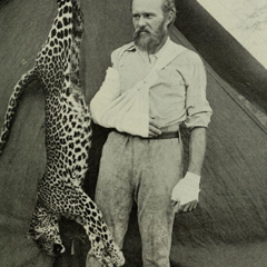 Caption: Famous taxidermist Carl Akeley posing with the leopard he killed with his bare hands