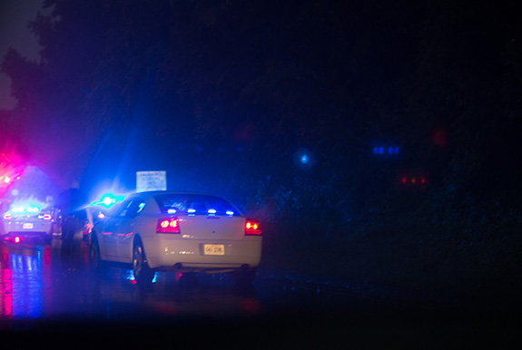 Caption: A police officer pulls over a driver on a dark rainy night, Credit: Tom Woodward/Flickr