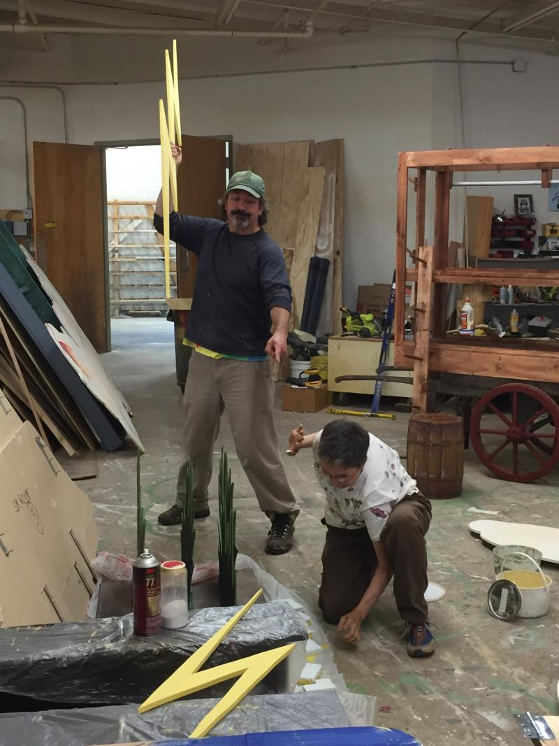 Caption: Cal Metts, artistic director of LOON, channels his inner Thor to speed up construction of the set. Volunteer Pat Castellano looks ... well, tres' uncomfortable., Credit: ©Ann Gumpper
