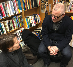 Caption: Virginia sits on the floor to interview Tom Perrotta at Harvard Book Store., Credit: Sara Plourde