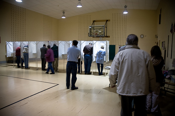 Caption: A row of voting booths are busy in a small gymnasium., Credit: Heather Katsoulis/Flickr