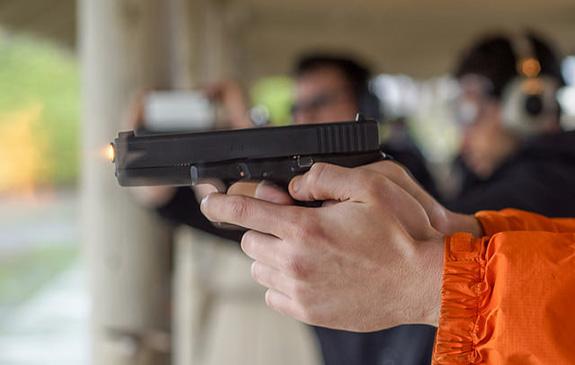 Caption: A handgun is gripped and being fired at a gun club range, Credit: Peretz Partensky/Flickr