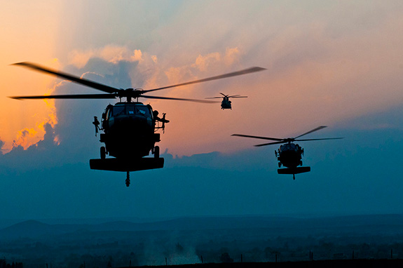 Caption: Three military style helicopters approach against a sunset lit sky., Credit: DVIDSHUB/Flickr