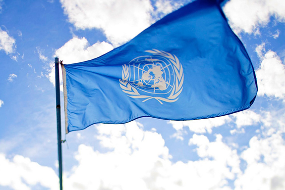 Caption: A blue UN flag flaps in the wind., Credit: Sanjitbakshi/Flickr