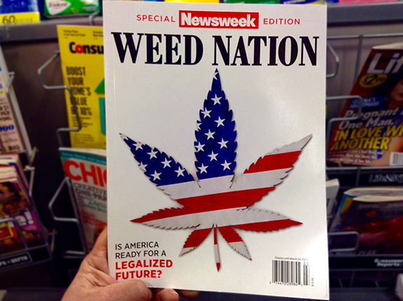 Caption: A hand holds up the Newsweek Weed Nation issue with a pot shaped american flag, Credit: Mike Mozart/Flickr