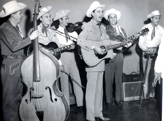 Caption: Tommy Jackson (3rd from left) was the fiddler who defined the Nashville session style, backing stars including Hank Williams and Ernest Tubb.  But he died nearly forgotten in 1979.  , Credit: findagrave.com & Kim Inboden.