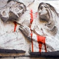 Caption: Jesus and Mary with red paint, sculptural relief on a Jerusalem building, Credit: Jake Warga