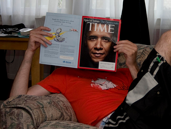 Caption: Brian Ambrozy/Flickr, Credit: President Obama on the front cover to Time is held up in front of someone's face lounging on the couch.