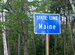 "Caption: A blue sign says ""STATE LINE: Maine"", Credit: Ken Lund/Flickr"