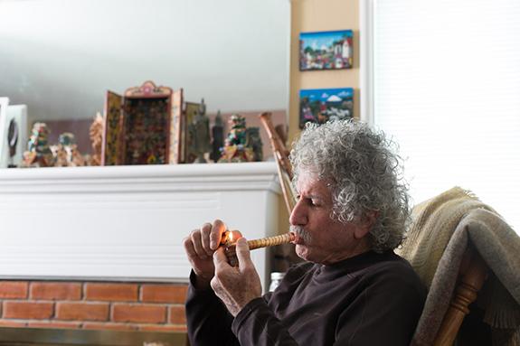 Caption: An older gentleman smokes marijuana through a bubbler sitting in his living room., Credit: Sonya Yruel/Drug Policy Alliance