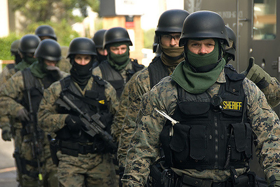 Caption: A group of masked SWAT team members march in a line during an exercise., Credit: Oregon Department of Transportation/Flickr