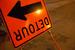 Caption: An orange upside down DETOUR sign points to the left. , Credit: Billie Grace Ward/Flickr