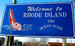 "Caption: A sea-blue ""Welcome to Rhode Island"" sign is shown close up. , Credit: Taber Andrew Bain/Flickr"