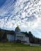 Caption: The Vermont state house sits on a green lawn as the blue cloud-speckled sky stretches out above its golden dome., Credit: LiftedVT/Instagram