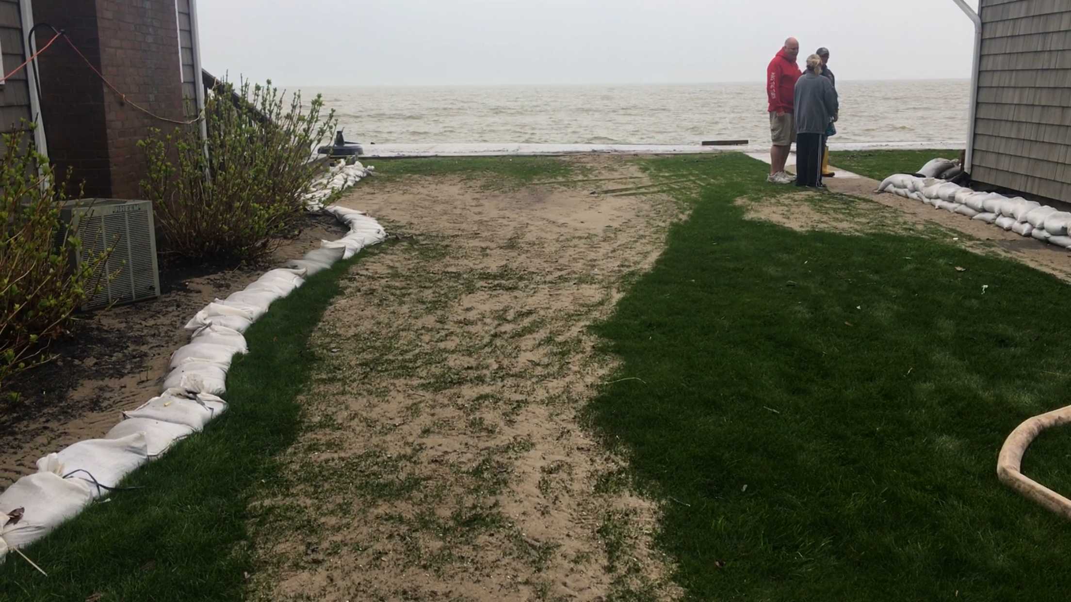 Caption: Residents assess the damage of flooding along the south shore of Lake Ontario., Credit: Veronica Volk