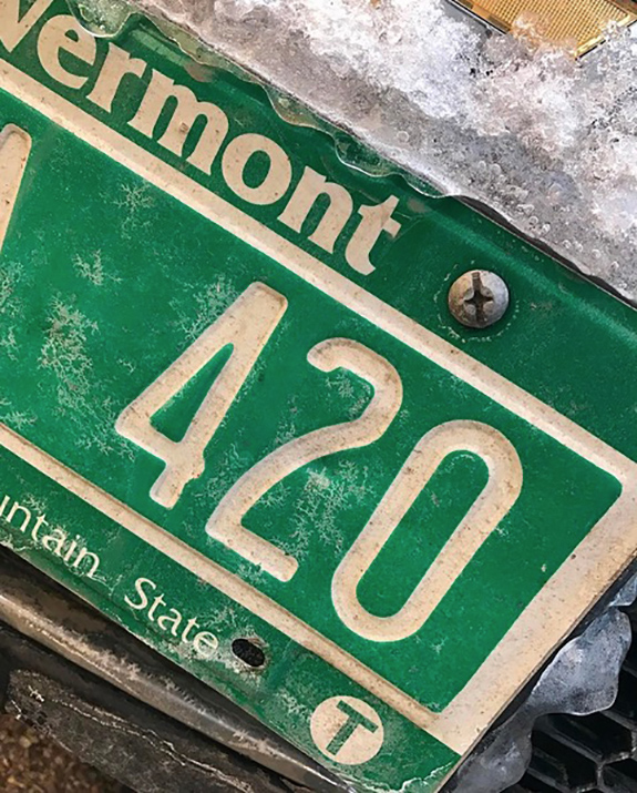 Caption: A close up photo of a green Vermont license plate with the last three digits '420'., Credit: LiftedVT/Instagram