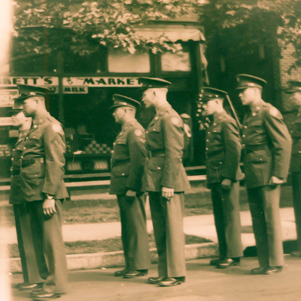 Caption: Funeral service in front of Barrett's Market 1942