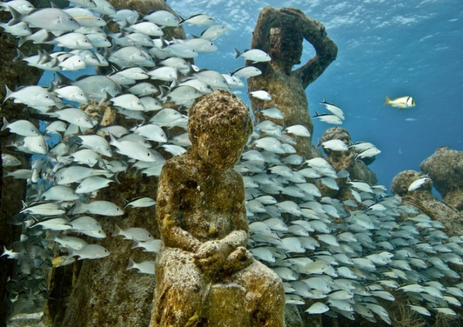 "Caption: ""Silent Evolution."" Installation at MUSA (Museo Subacuático de Arte, Cancun, Isla Mujeres, Mexico.) The sculptural works of Jason deCaires Taylor serve as artificial reefs, providing habitat for fish and other ocean species. For more information visit his, Credit: Jason deCaires Taylor"