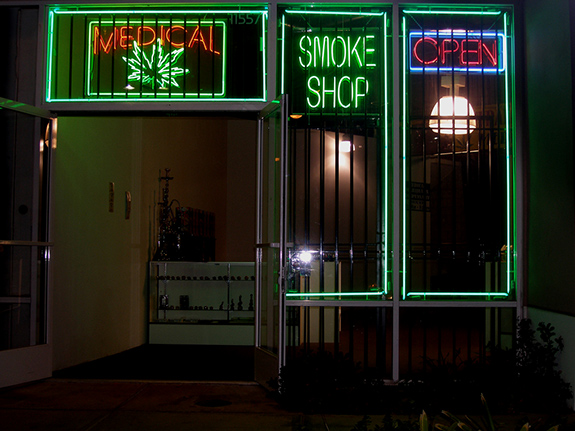 Caption: A medical marijuana store front mixes bright neon lights with stout safety bars over the windows., Credit: Laurie Avacado/Flickr