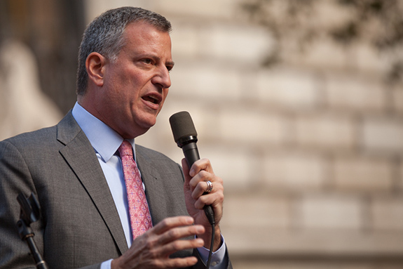 Caption: New York City Mayor Bill de Blasio speaks while holding a microphone and wearing a gray suit., Credit: Kevin Case/Flickr