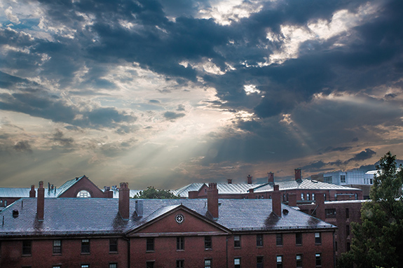 Caption: The sun breaks through a scattered covering of dark blue clouds over a field of brick buildings topped with shining reflective roofs., Credit: Tim Sackton/Flickr