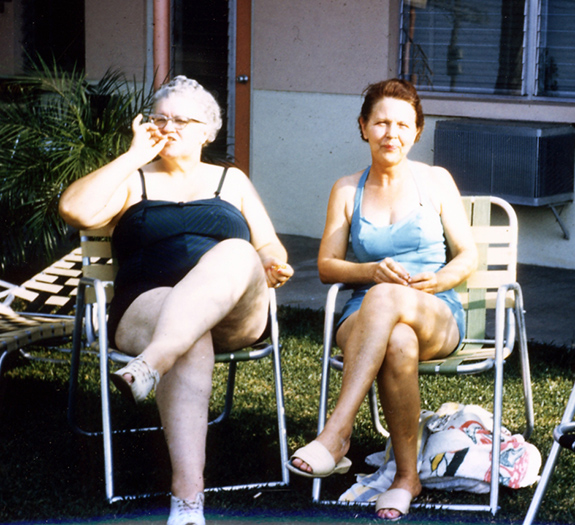 Caption: A photo taken in the 70s in Hawaii by a family on vacation show two women sitting in beach chairs in a sunny backyard, with the oldest women, in white hair, appearing to take a pull on a nearly-completed marijuana cigarette., Credit: Ted Drake/Flickr