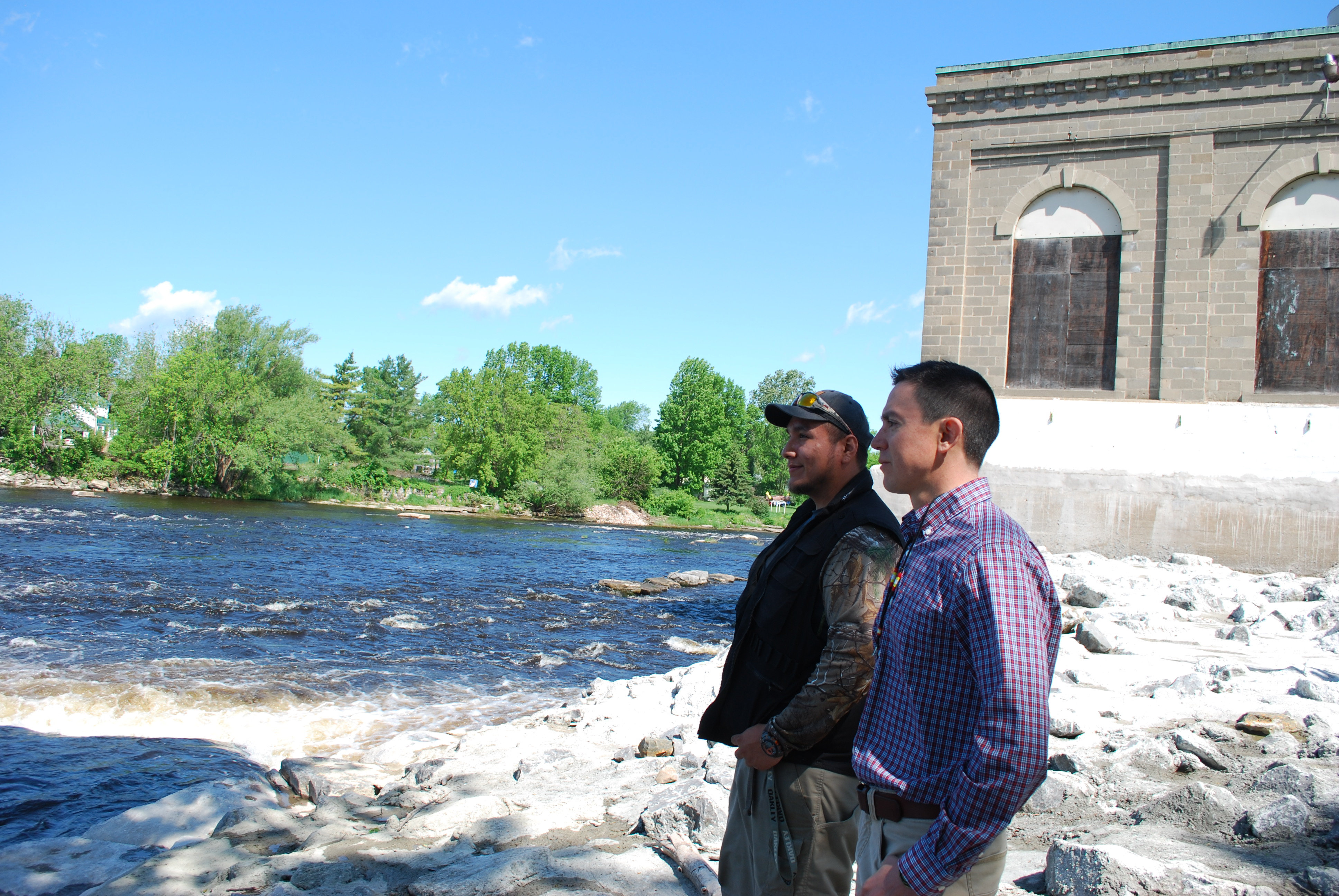 Caption: Tony David (right) and an apprentice, Angelo Johnson (left) look out over the water where the dam used to be., Credit: Veronica Volk