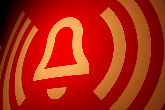 Caption: A graphic of a yellow alert logo on a red background sits askew., Credit: Martin Abegglen/Flickr