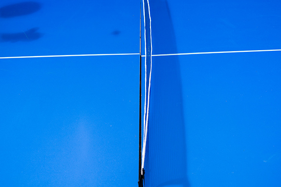 Caption: An abstract photo shot overhead shows a blue ping pong table with the shadow of a flying ball and player showing on the right side of the frame., Credit: Phil Roeder/Flickr