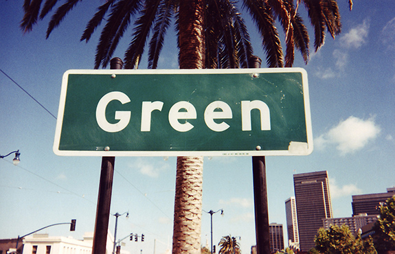 Caption: A street sign reading 'Green' is affixed to a palm tree and sits against a washed out blue sky., Credit: Lenny DiFranza/Flickr