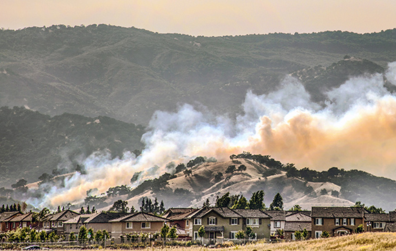 Caption: Mountains rise behind a line of houses with wildfire smoke pouring off hidden fire just over the crest from the homes., Credit: Robert Couse-Baker/Flickr