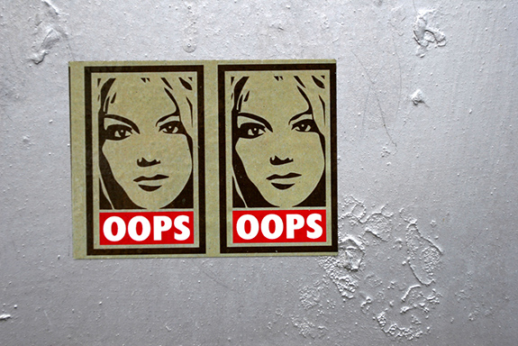 Caption: Two one-tone graphic posters of Britney Spears above the words 'oops' are plastered to a bumpy rough white wall., Credit: Stephen Harlan/Flickr