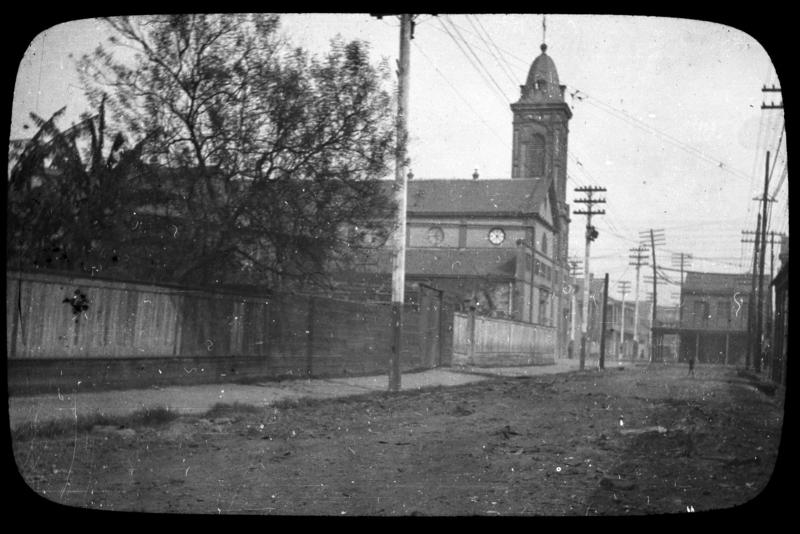 Caption: Coverglass and matt bound together with black paper tape. View looking along the 1200 block of Governor Nicholls Street in Treme, with the church visible in midview. , Credit:  The Historic New Orleans Collection, Gift of Mrs. Joy Segura, acc. no. 2004.0096.68