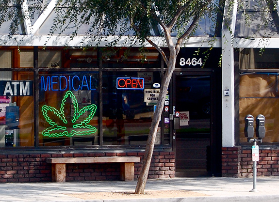 Caption: A neon medical marijuana sign sits in a glass storefront next to another neon sign reading 'Open'., Credit: Katheirne Hitt/Flickr