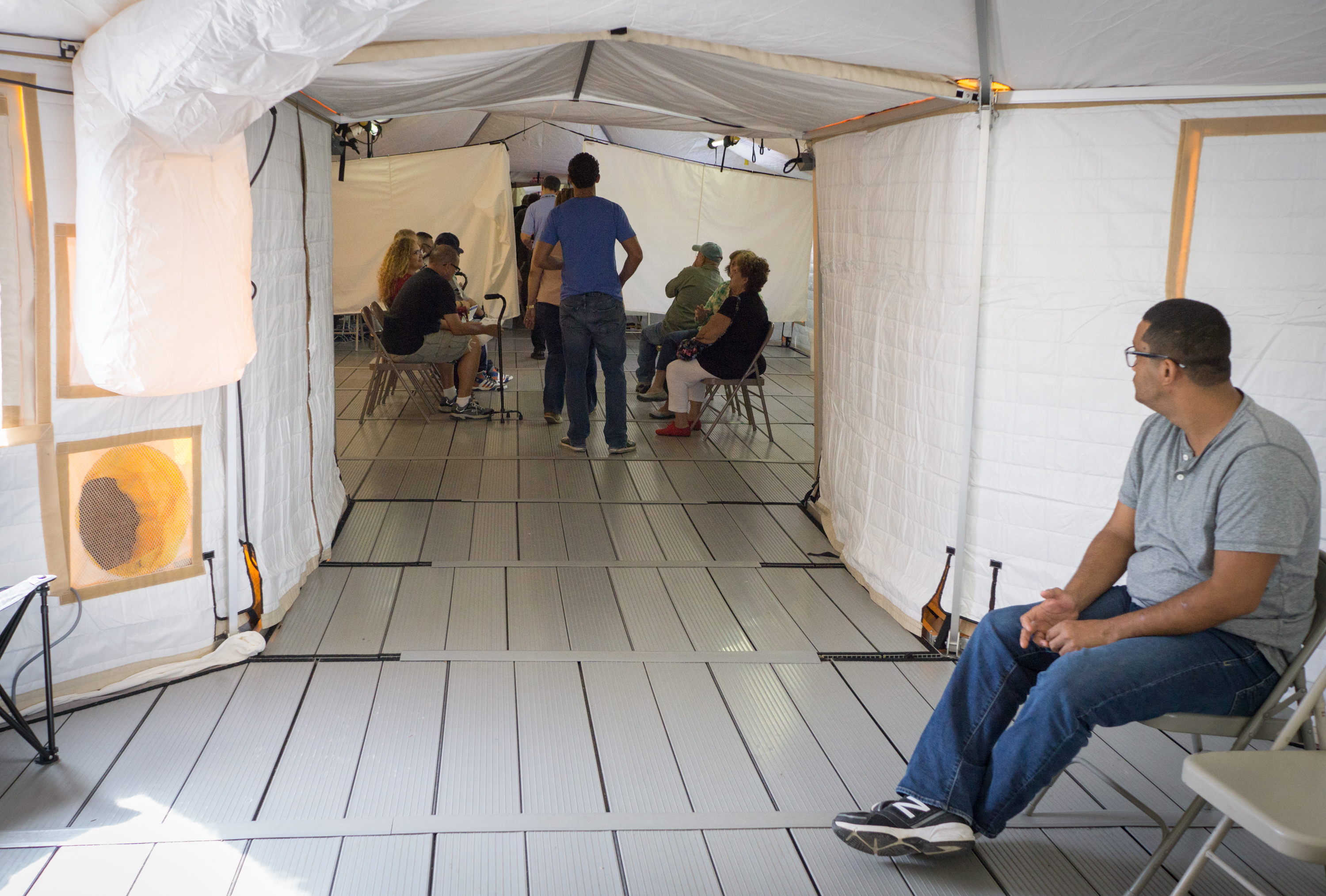 Caption: Patients wait for medical care at a temporary hospital tent outside the VA hospital in Ponce, Puerto Rico. The main building is unusable after Hurricane Maria., Credit: Angel Valentin/American Homefront