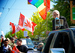 Caption: A red Canadian pot leaf flag waves in the sunlight as activists march in parade., Credit: Cannabis Culture/Flickr