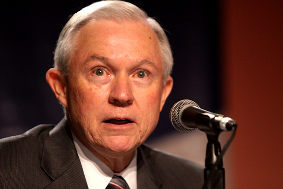 Caption: Attorney General Jeff Sessions speaks seated at a table in front of a microphone. , Credit: Gage Skidmore/Flickr