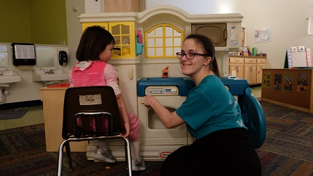 "Caption: Maggie McCrumb plays with a child at a day care center while being assessed by a ""vocational evaluator,"" in order to get help with job placement from New York state., Credit: KAREN SHAKERDGE/WXXI NEWS"