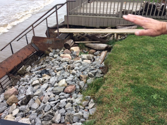 Caption: A lawn that once stretched to the iron gate has ben eroded by high waters., Credit: Caitlin Whyte
