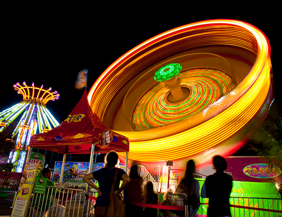 Caption: An amusement park ride spins itself into a bright bottle cap shape as onlookers as lost in a blur of time., Credit: Elia Scudiero/Flickr