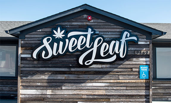 Caption: A Sweet Leaf sign sits on an exterior wall of vertically running aged wooden slats., Credit: Sweet Leaf Dispensary