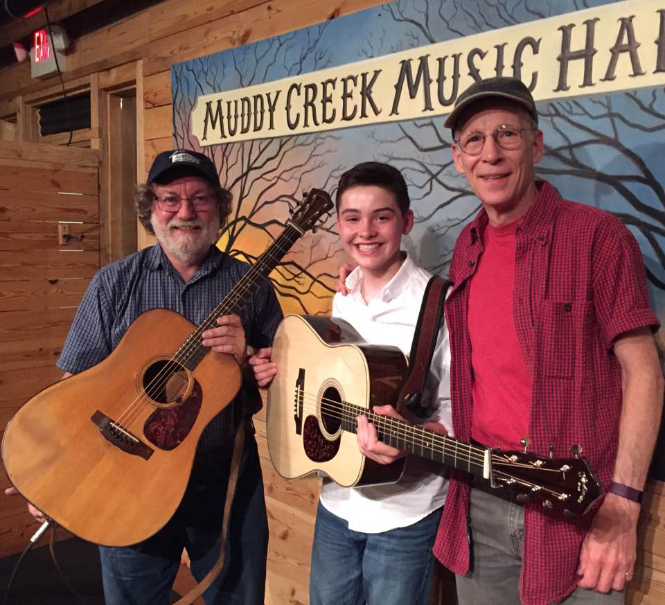 Caption: Wayne Henderson (left) and Presley Barker (center) with ATBR host Paul Brown at Muddy Creek Music Hall.  This week's show presents excerpts from their July, 2017 performance.  Daniel Greeson joins Wayne and Presley on fiddle for a tune as well.  , Credit: Shana Whitehead