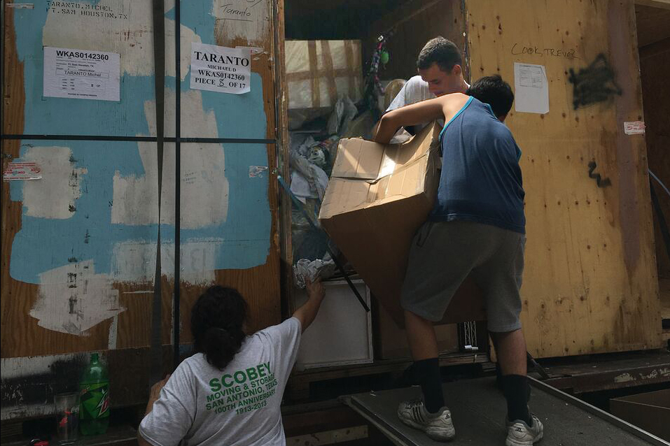 Caption: Movers unpack a van at Sarah Taranto's house in May 2017. Many of the Tarantos' possessions arrived damaged, while other had been stolen during the moving process., Credit: Sarah Taranto